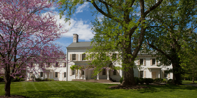 Scenic front landscape photo of the Morven Museum and Garden with blooming trees in front of the building.
